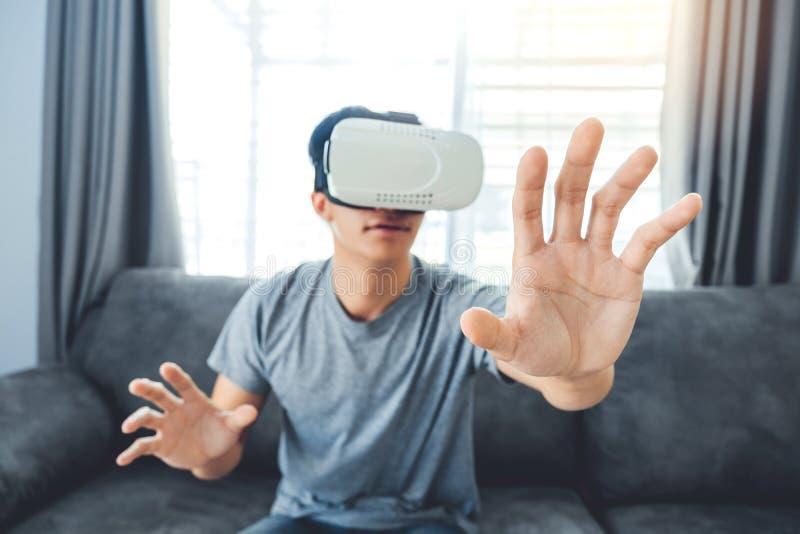 Молодой человек используя стекла виртуальной реальности имея потеху с имитатором VR дома стоковые изображения