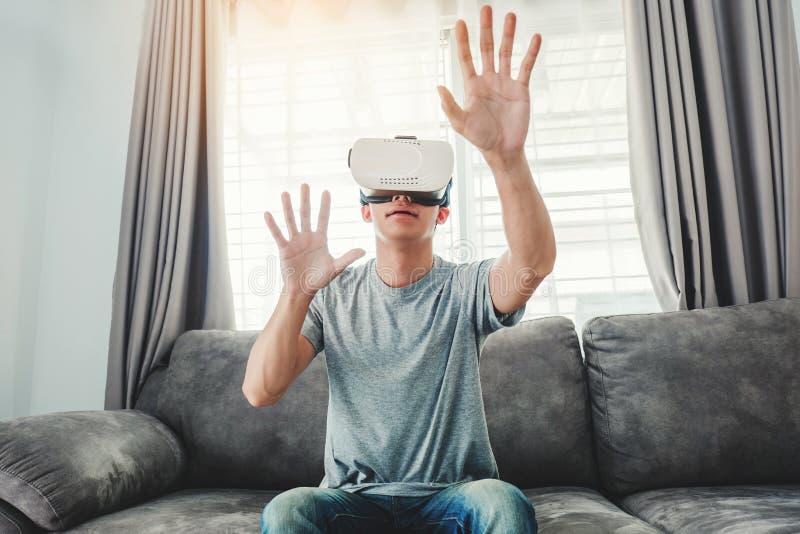 Молодой человек используя стекла виртуальной реальности имея потеху с имитатором VR дома стоковое изображение rf