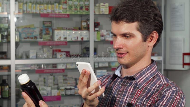 Молодой человек используя умный телефон пока ходящ по магазинам на фармации стоковое фото