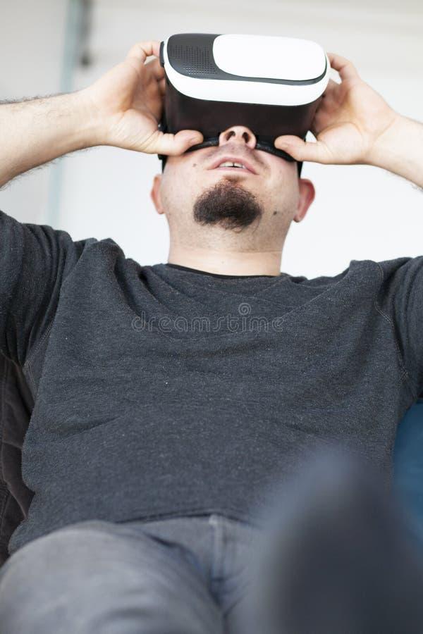 молодой человек используя шлемофон виртуальной реальности стоковое фото