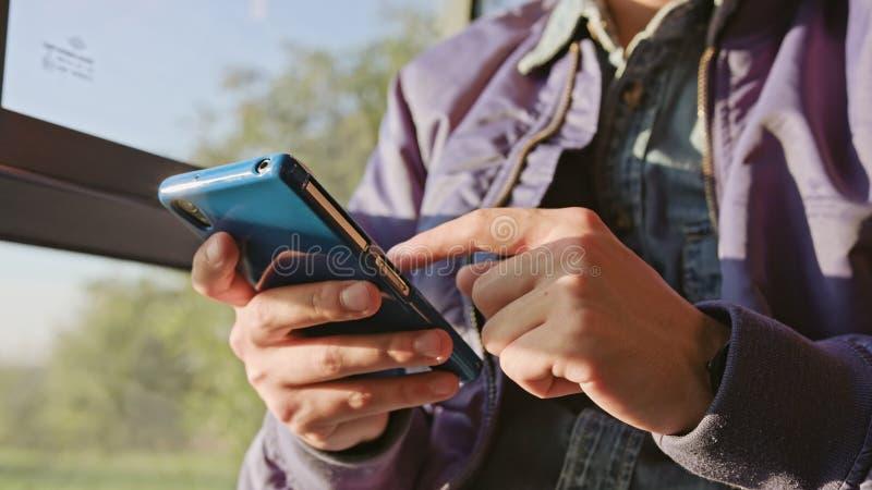 Молодой человек используя Smartphone на шине стоковые фотографии rf
