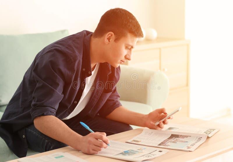 Молодой человек ища classifieds в газете дома стоковое фото rf