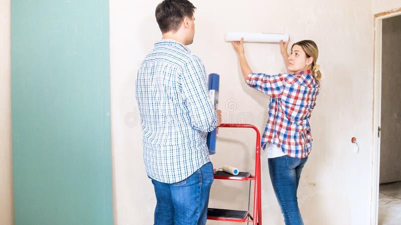 Молодой человек и женщина выбирая обои в их новой квартире стоковая фотография