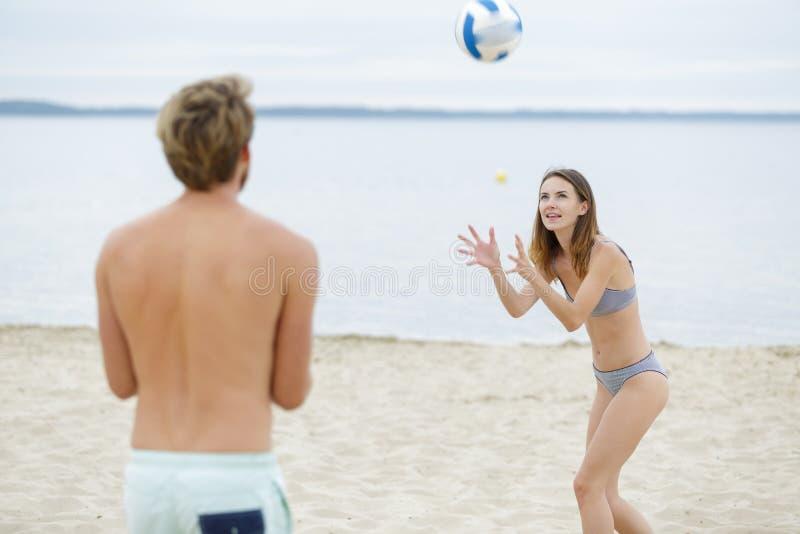 Молодой человек и женщина играя пляжный волейбол совместно стоковая фотография rf