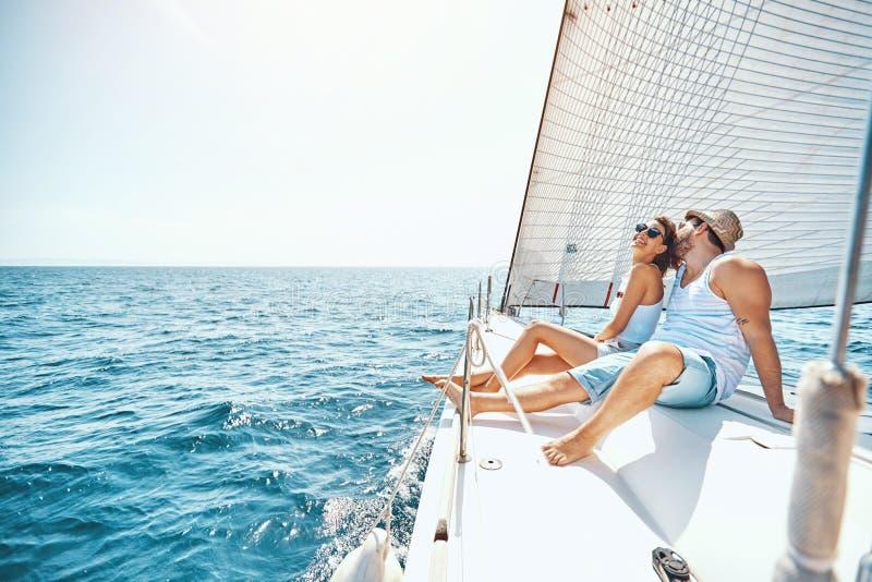 Молодой человек и женщина ослабляя на яхте стоковые изображения rf