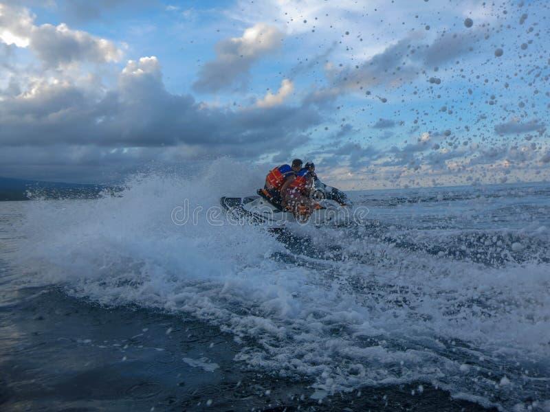 Молодой человек и женщина перемещаясь через поверхность моря Люди на водных лыжах имеют потеху в океане Водитель в действии во вр стоковое фото rf