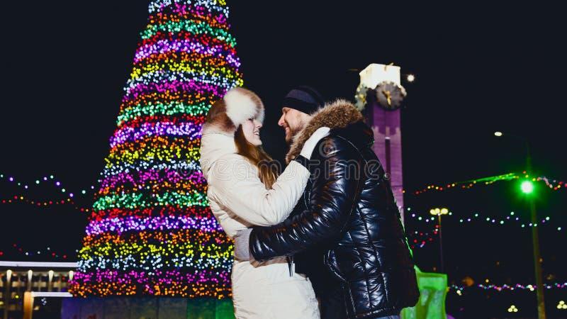 молодой человек и женщина прижимаясь под перезвонами на ночи рождества стоковые изображения