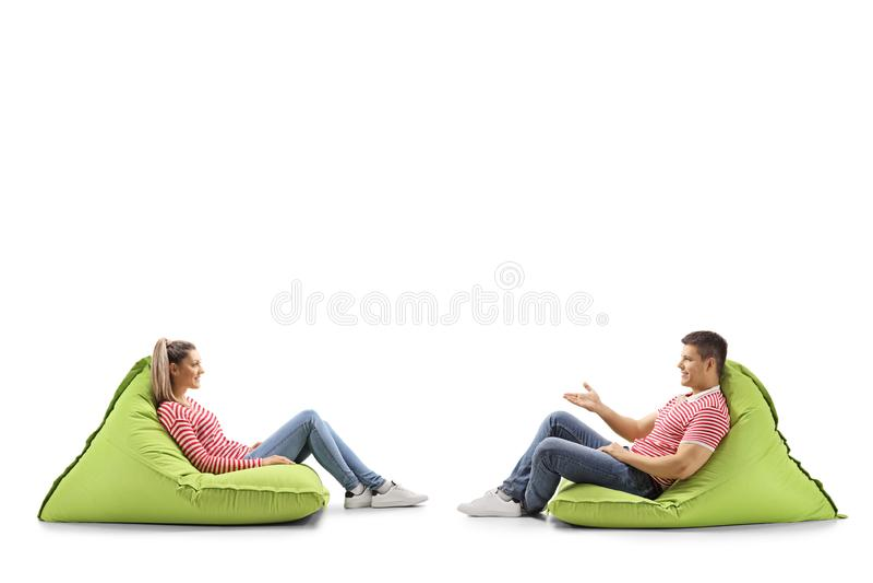 Молодой человек и женщина сидя на сумках и говорить фасоли стоковое фото