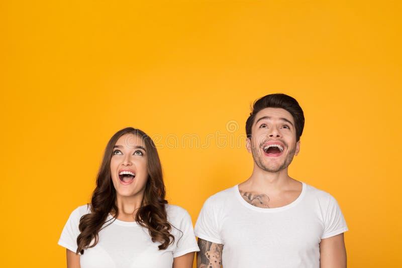 Молодой человек и женщина смотря вверх в ободрении стоковое изображение rf