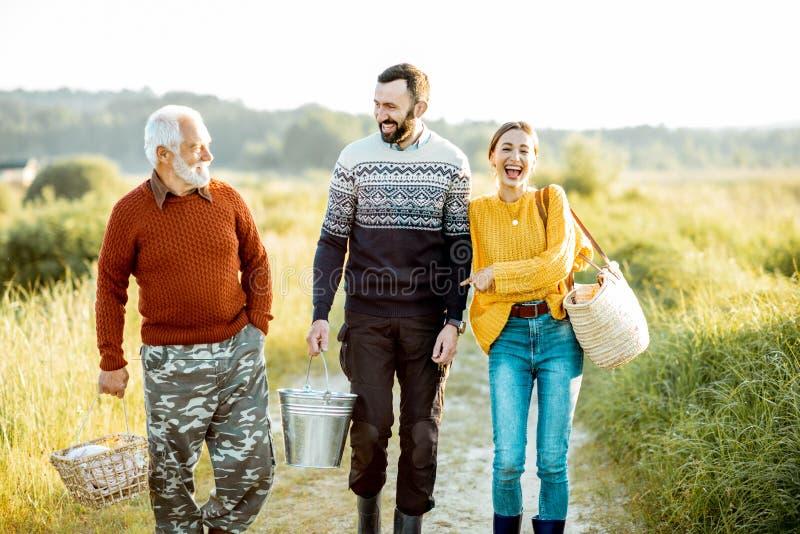 Молодой человек и женщина со старшим дедом идя outdoors стоковые изображения rf