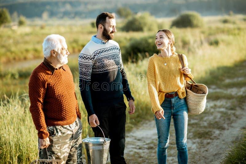 Молодой человек и женщина со старшим дедом идя outdoors стоковые изображения