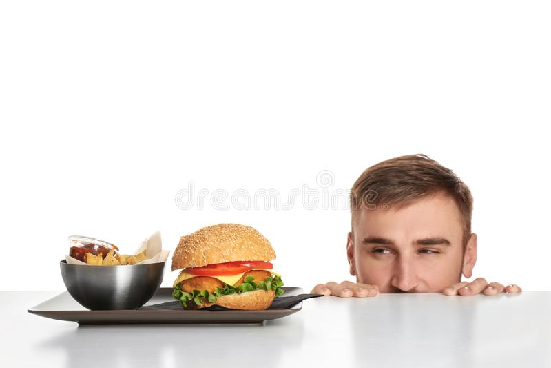 Молодой человек и плита с французским картофелем фри и вкусным бургером стоковые изображения rf