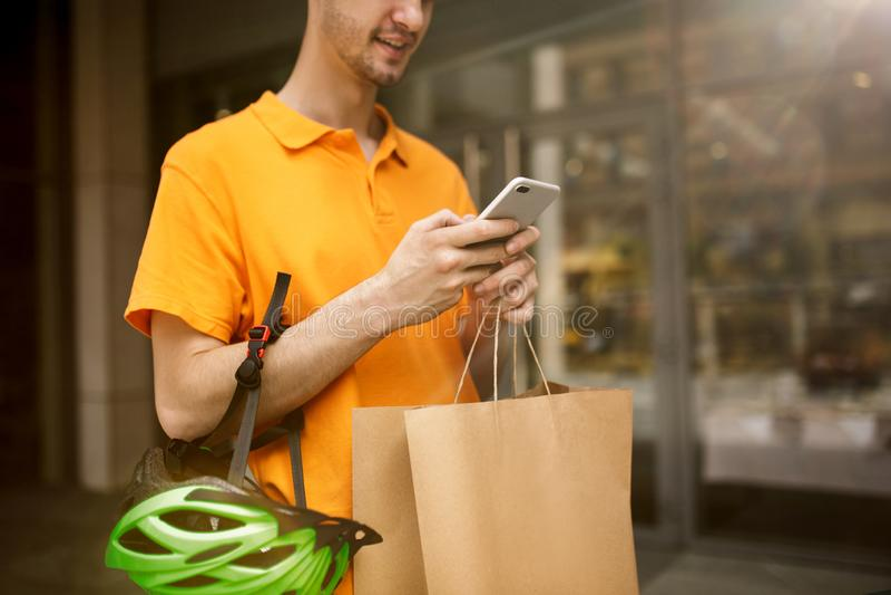 Молодой человек как курьер поставляя пакет используя устройства стоковые фотографии rf