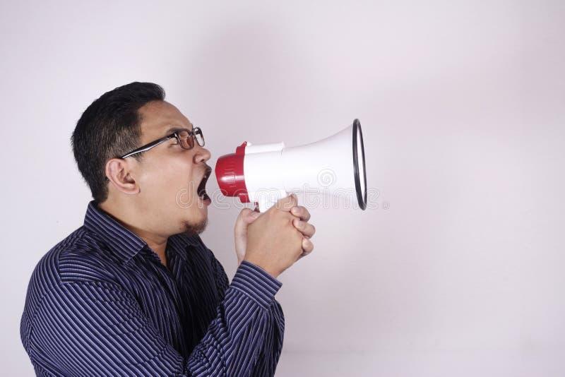 Молодой человек крича с мегафоном, сердитым выражением стоковые фотографии rf