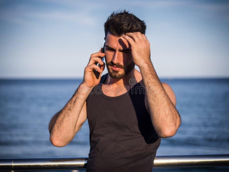 Молодой человек морем говоря на мобильном телефоне стоковое фото