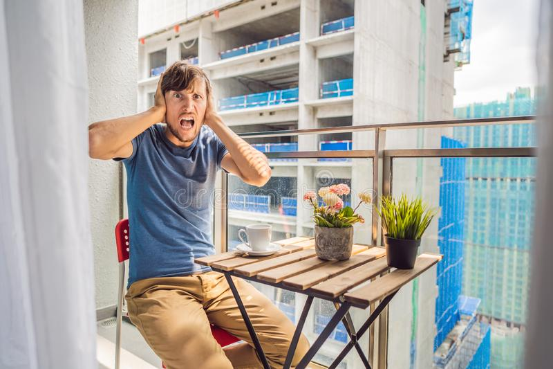 Молодой человек на балконе надоеданном работами здания снаружи Концепция шума Загрязнение воздуха от пыли здания стоковое фото