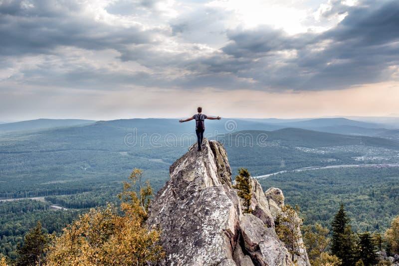 Молодой человек на горном пике стоковое фото