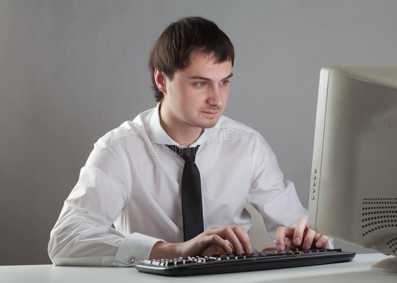 Молодой человек на компьютере стоковая фотография