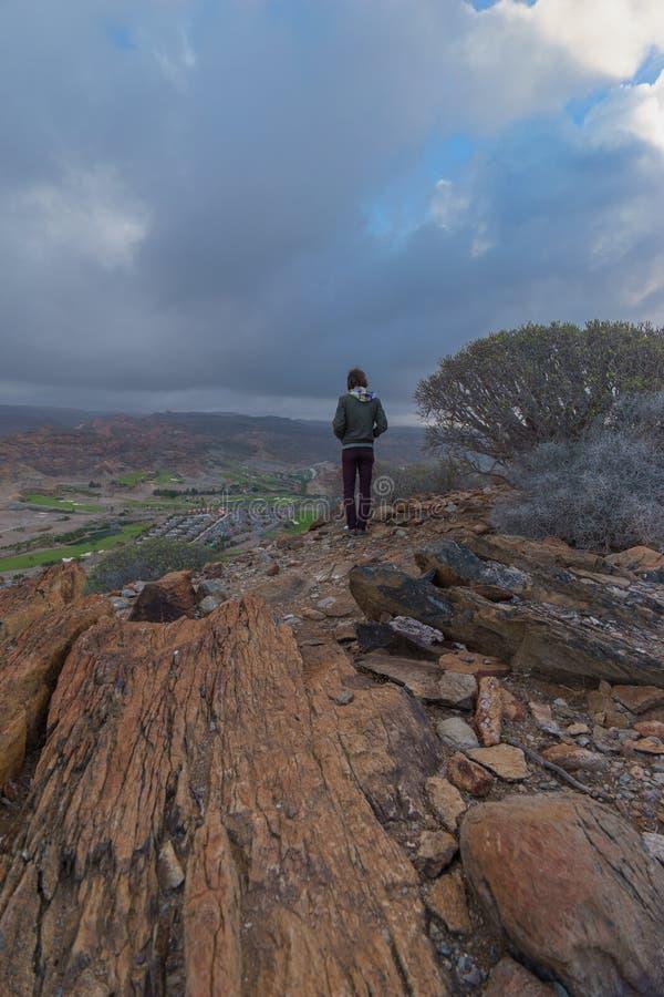 Молодой человек на краю горы стоковое изображение rf