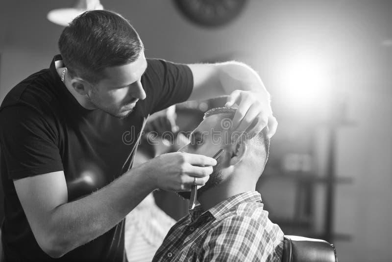 Молодой человек на парикмахерскае стоковые изображения