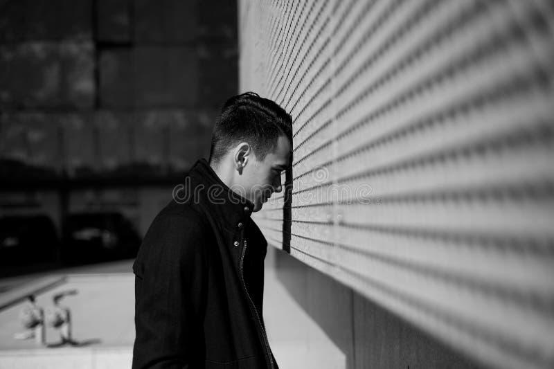 Молодой человек несчастн в мертвом конце или депрессии Стойки полагаясь его лоб против стены черная белизна стоковое изображение