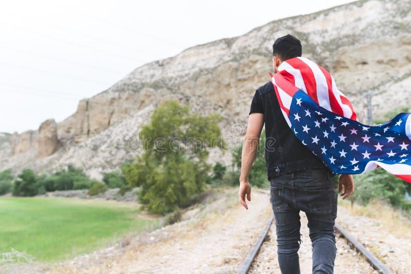 Молодой человек нося американский флаг 4-ого июля стоковое фото
