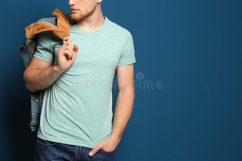 Молодой человек нося пустую футболку на голубой предпосылке, крупном плане Модель-макет для стоковая фотография