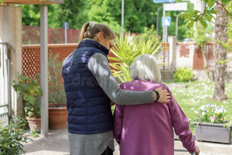 Молодой человек осуществляющий уход идя с пожилой женщиной в саде стоковые фото