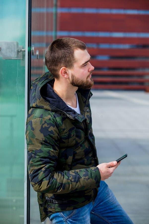 Молодой человек отправляя SMS на мобильном телефоне на улице города стоковые фотографии rf