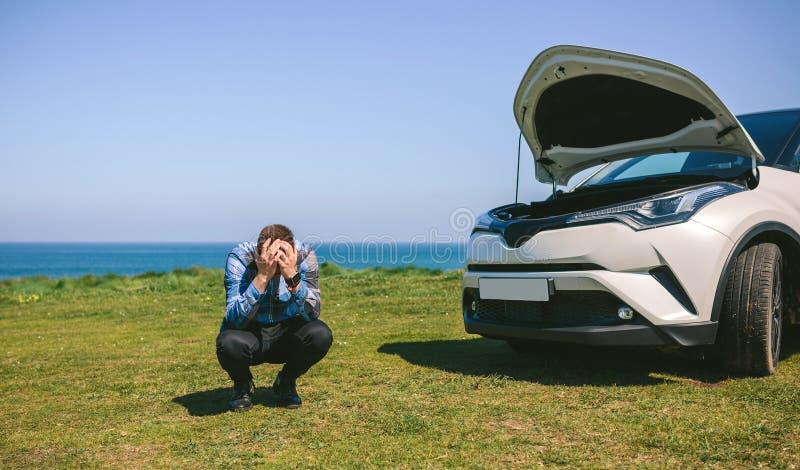 Молодой человек отчаянный, автомобиль сломанный вниз стоковые фотографии rf