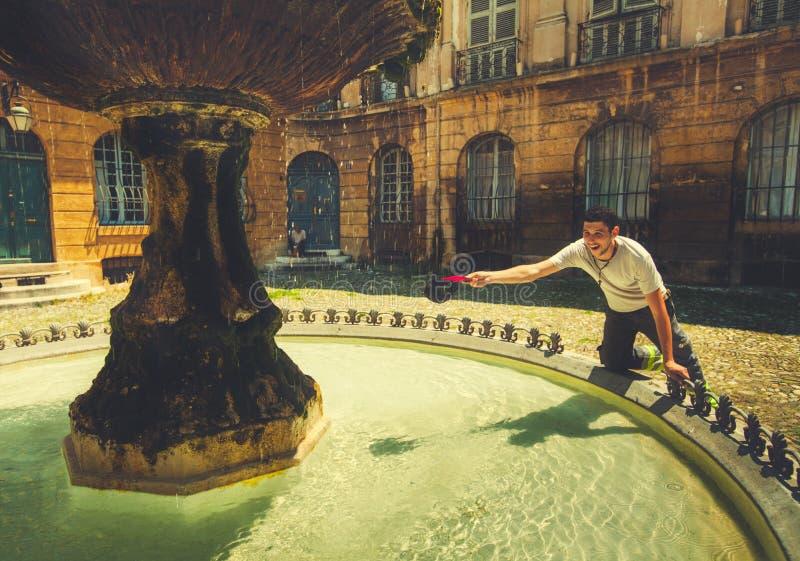Молодой человек охлаждает в фонтане стоковые фото