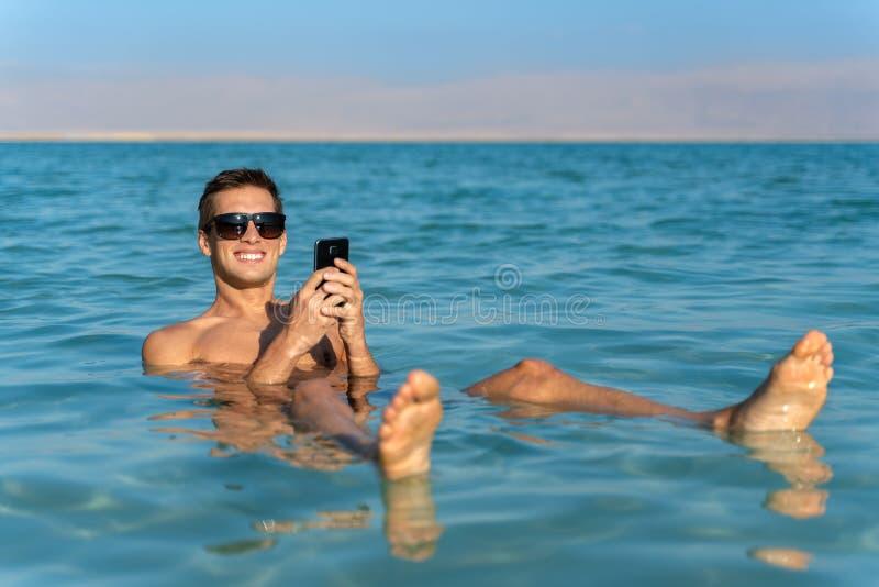 Молодой человек плавая на поверхность воды мертвого моря и используя его смартфон стоковая фотография