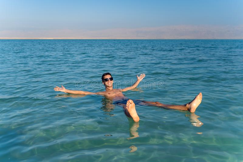 Молодой человек плавая на поверхность воды мертвого моря стоковая фотография rf