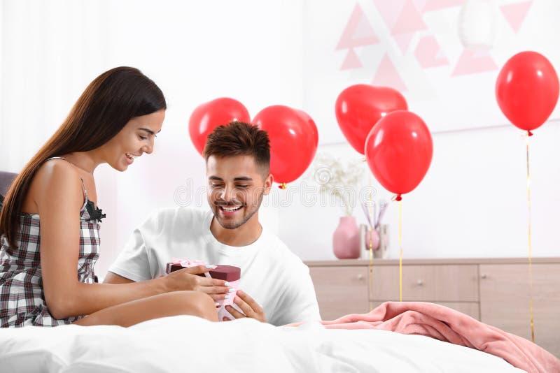 Молодой человек, подаривший подарок своей девушке, украшен воздушными шариками Празднование Дня Святого Валентина стоковая фотография rf