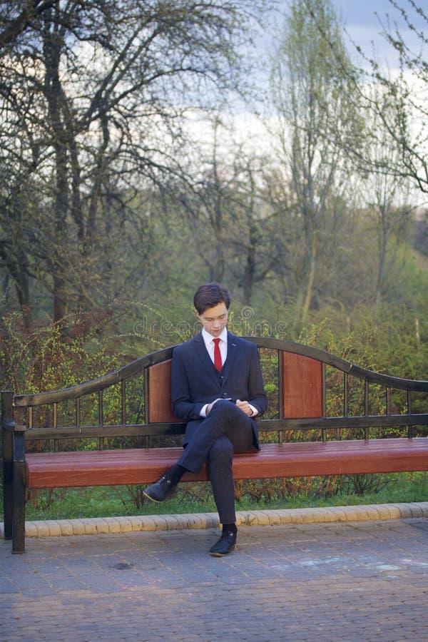 Молодой человек, подросток, в классическом костюме Сидит на винтажном стенде в парке весны Он держит smartphone в его руках и смо стоковое фото rf