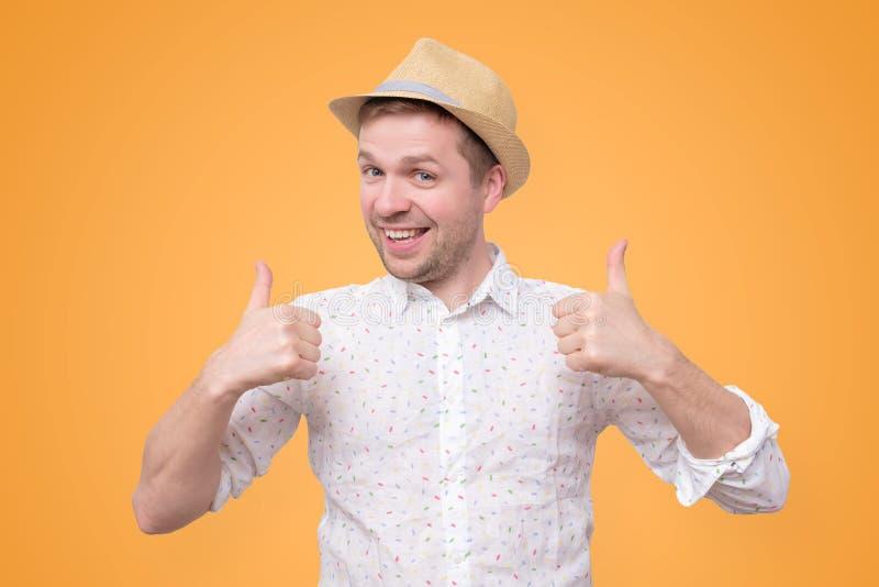 Молодой человек показывая большие пальцы руки вверх по давать совет стоковая фотография