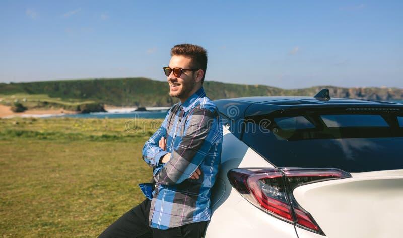 Молодой человек полагаясь на его автомобиле стоковые изображения