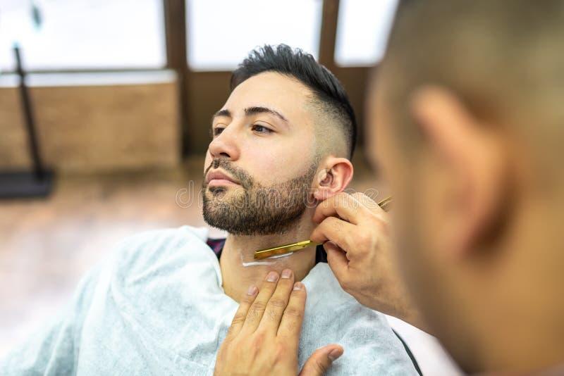 Молодой человек получая бороду побритый стоковое фото rf