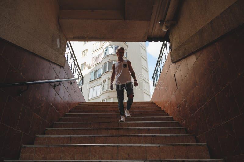 Молодой человек получая вниз с лестниц в пешеходном метро стоковые фото