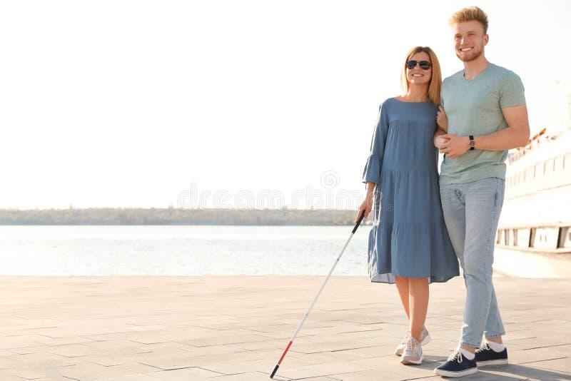 Молодой человек помогая слепому человеку с длинной тросточкой в городе стоковая фотография