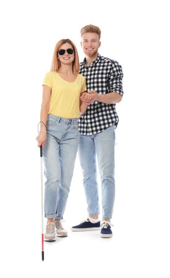 Молодой человек помогая слепому человеку с длинной тросточкой стоковое изображение