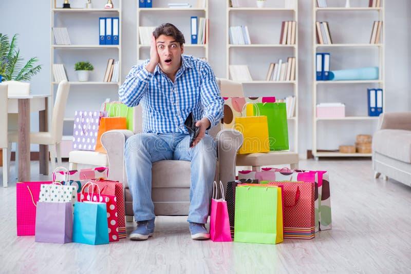 Молодой человек после чрезмерно ходить по магазинам дома стоковая фотография rf