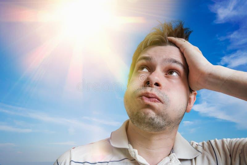 Молодой человек потеет Концепция жаркой погоды Солнце в предпосылке стоковые изображения rf