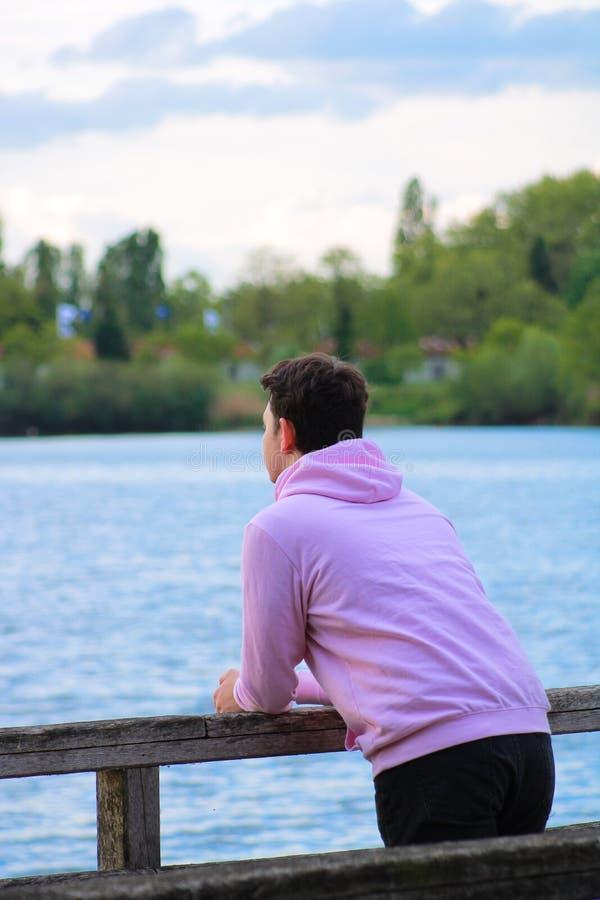 Молодой человек предусматривая озеро стоковые изображения rf