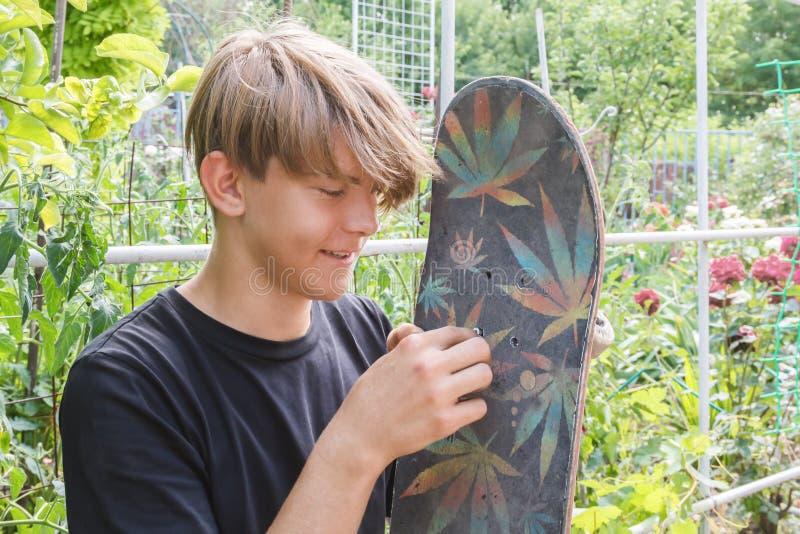 Молодой человек приниманся за ремонтируя скейтборд в саде outdoors стоковое фото