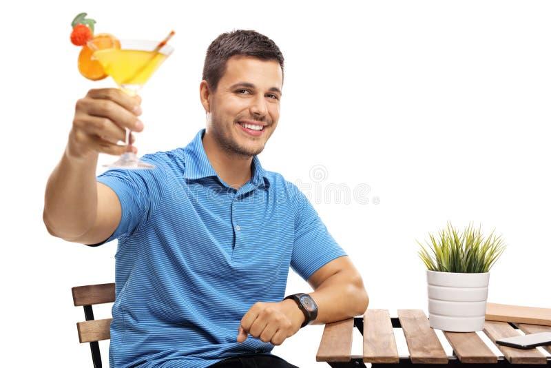 Молодой человек при коктеиль сидя на таблице стоковые изображения