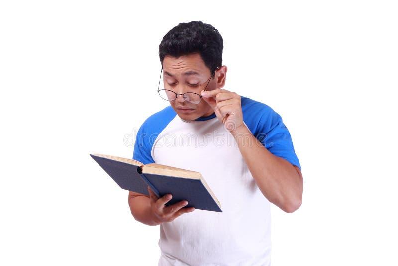 Молодой человек при стекла имея плохое зрение когда книга чтения стоковые фотографии rf