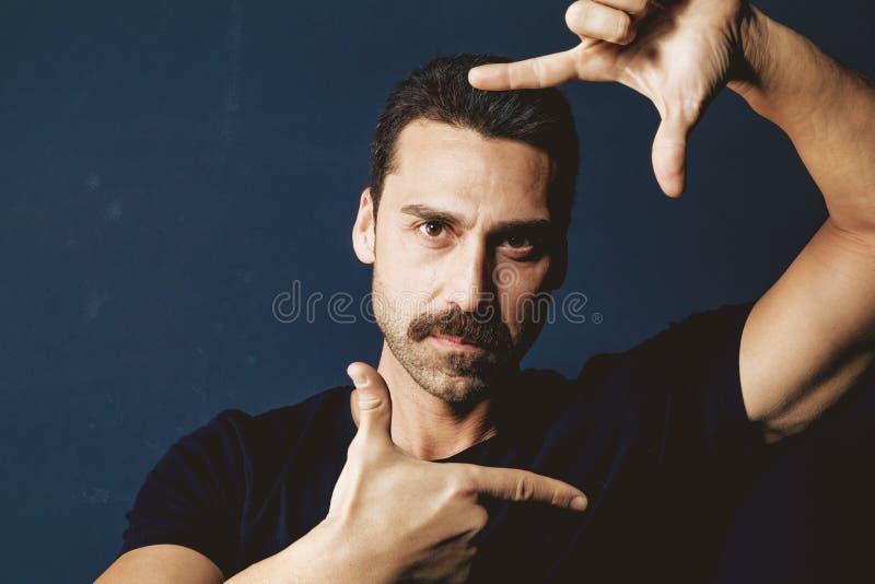 Молодой человек при усик обрамляя его сторону с его руками стоковое изображение