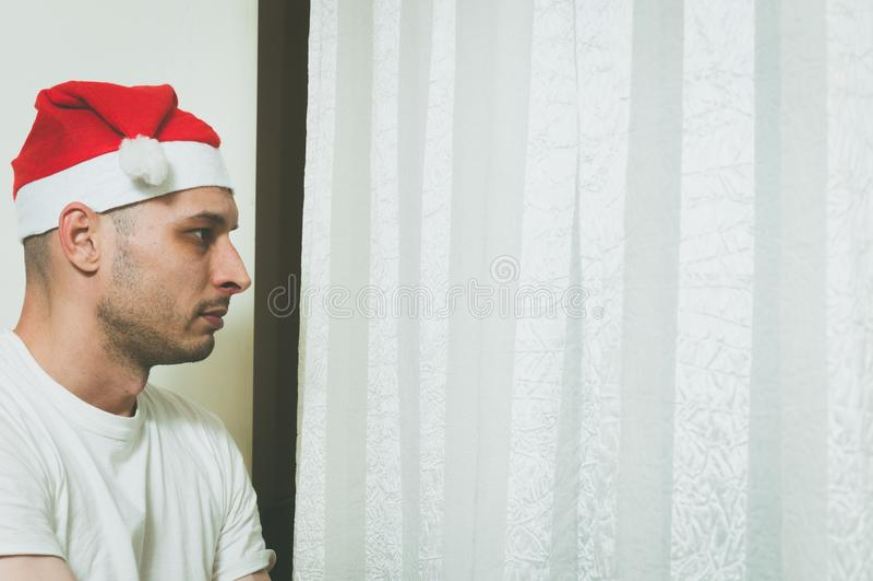 Молодой человек при шляпа Санта Клауса смотря через окно чувствуя сиротливый и унылый на концепция депрессии праздник Нового Года стоковые изображения rf