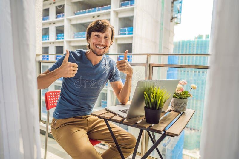 Молодой человек пробуя работать на балконе надоеданном работами здания снаружи Концепция шума Загрязнение воздуха от стоковая фотография